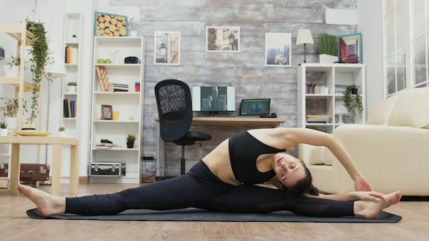 Flessibile giovane donna in piedi in slip sulla stuoia di yoga che raggiunge per il suo piede.