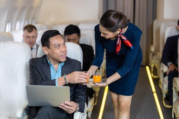 Assistente di volo che serve, assistente di volo femminile asiatica che serve drink ai passeggeri in aereo, equipaggio di cabina o hostess che lavora in aereo.