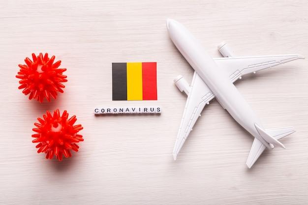Divieto di volo e frontiere chiuse per turisti e viaggiatori con coronavirus covid-19. aeroplano e bandiera del belgio su un bianco