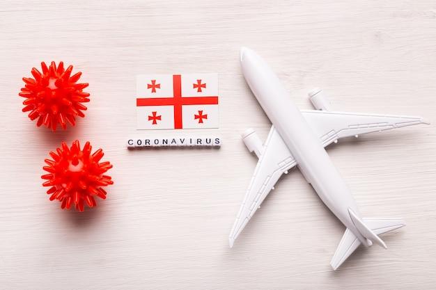 Divieto di volo e frontiere chiuse per turisti e viaggiatori con coronavirus covid-19. aeroplano e bandiera della georgia su un bianco