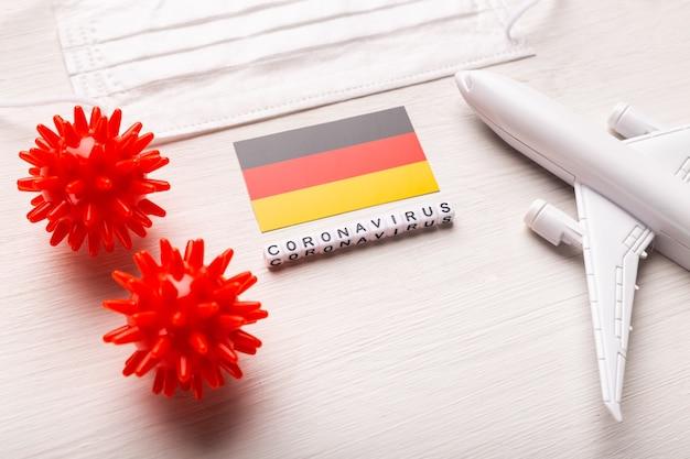 Divieto di volo e frontiere chiuse per turisti e viaggiatori con coronavirus covid-19. aeroplano e bandiera della germania su un bianco