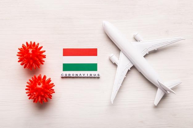 Divieto di volo e frontiere chiuse per turisti e viaggiatori con coronavirus covid-19. aeroplano e bandiera dell'ungheria su una priorità bassa bianca. pandemia di coronavirus.
