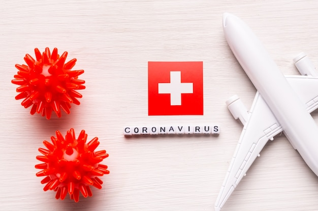 Divieto di volo e frontiere chiuse per turisti e viaggiatori con coronavirus covid-19. aeroplano e bandiera della svizzera su un bianco