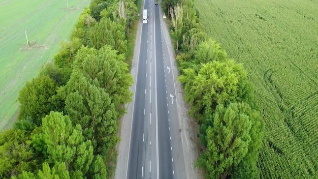Volo sopra la crema degli alberi lungo l'autostrada. autostrada con traffico intenso.