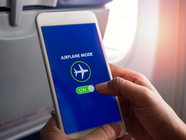 Concetto di modalità di volo. passi la tenuta dello smartphone bianco e accenda la modalità dell'aeroplano sullo schermo vicino alla finestra sull'aeroplano.