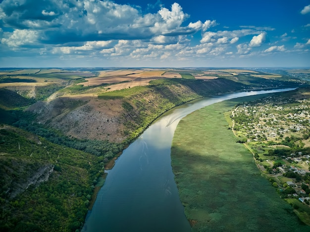 Volo attraverso il maestoso fiume dnister, la lussureggiante foresta verde e il villaggio. moldova, europa. fotografia di paesaggi.