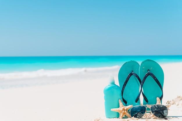 Flip flop, bottiglie di crema solare, occhiali di protezione, stelle marine e occhiali da sole sull'oceano di sfondo spiaggia di sabbia bianca