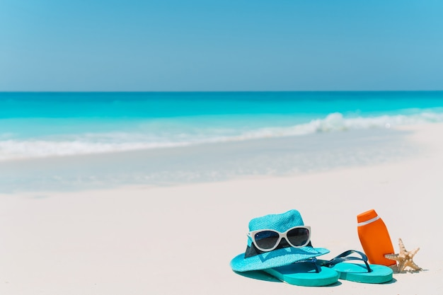Flip flop, bottiglie di crema solare, occhiali, stelle marine e occhiali da sole sulla spiaggia di sabbia bianca dell'oceano