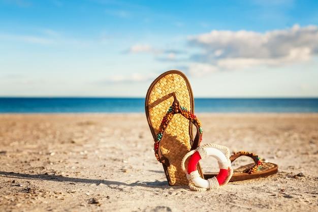 Infradito e salvagente sulla spiaggia di sabbia. vacanze estive sul mar baltico, germania. concetto di sicurezza