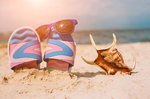 Infradito nella sabbia sulla spiaggia. occhiali da sole su di esso. concetto di vacanza estiva. riva del mare