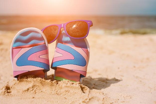 Infradito nella sabbia sulla spiaggia. occhiali da sole su di esso. concetto di vacanza estiva