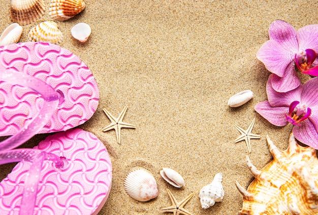 Infradito nella sabbia con stelle marine e fiori di orchidea