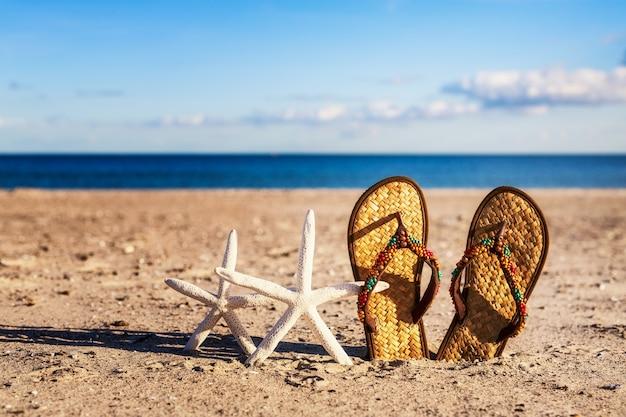 Infradito e stelle marine sulla spiaggia di sabbia. vacanze estive sul mar baltico, concetto della germania