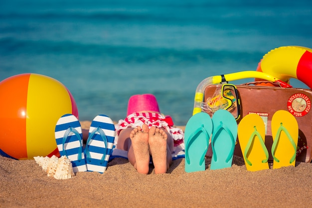 Infradito e piedi dei bambini sulla spiaggia concetto di vacanza estiva