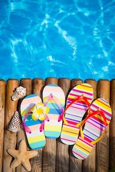 Infradito su legno contro acqua blu vacanze estive concept