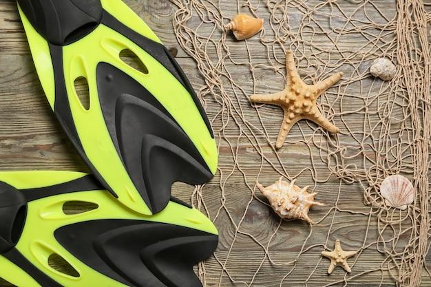 Pinne, calze a rete e decorazioni marine su fondo in legno