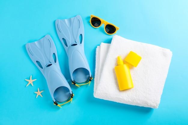 Pinne, occhiali da sole, asciugamano e stelle marine sulla tabella dei colori