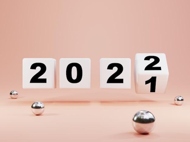 Capovolgimento del blocco cubo bianco per il cambiamento dal 2021 al 2022 su sfondo rosa pastello con palline metalliche, buon natale e felice anno nuovo dal concetto di rendering 3d.