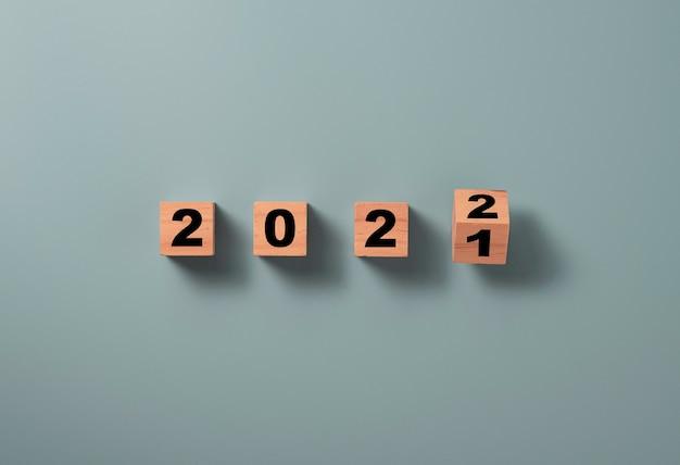 Capovolgere il cubo di blocco di legno per cambiare il 2021 al 2022 su sfondo blu, buon natale e felice anno nuovo concetto di preparazione.