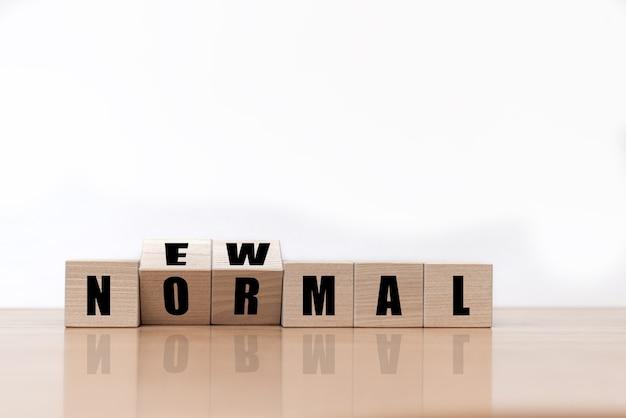 Ribaltando i cubi del blocco di legno per il nuovo funzionamento normale. il mondo sta cambiando per bilanciarlo in una nuova normalità inclusa.