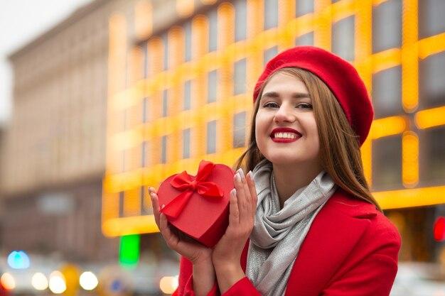 Flirty carina giovane donna che tiene una scatola regalo di san valentino a forma di cuore con un fiocco su uno sfondo di luci sfocate. spazio vuoto