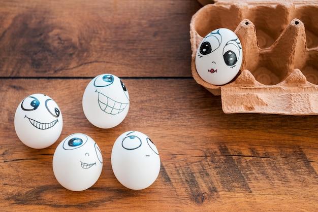 Uova civettuole. vista dall'alto di uova divertenti con diverse emozioni che flirtano con uova femminili che depongono in un contenitore sulla scrivania di legno
