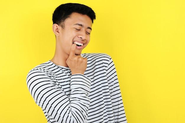 Flirty di bel giovane uomo asiatico che morde il dito, isolato su sfondo giallo