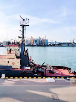 Gru da carico galleggiante, assistenza rimorchiatore sul molo in porto, porto marittimo cargo sul mare
