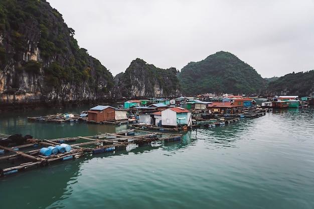 Allevamento ittico galleggiante nella baia di ha long, vietnam. povero, indigente. produzione di pesce e crostacei in mare.