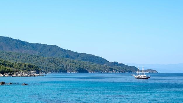 Barca a vela galleggiante nel mar egeo con uccelli sulla superficie dell'acqua di fronte e terra grecia