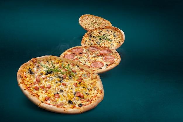 Pizze italiane galleggianti e fumanti su uno sfondo turchese con diversi condimenti. pizza appena sfornata con copia spazio per testo o design