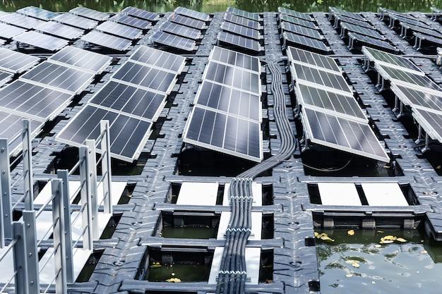 Pannelli solari galleggianti o piattaforma a celle solari sullo stagno del lago d'acqua per il risparmio dell'innovazione tecnologica energetica.