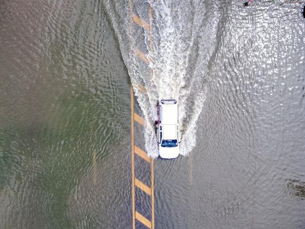 Strade allagate, persone con auto che passano. la fotografia aerea dei droni mostra le strade allagate e le auto delle persone che passano, spruzzi d'acqua.