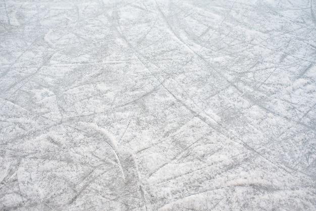 Fondo del pavimento di una pista di pattinaggio sul ghiaccio con segni di skate, con neve bianca durante l'inverno.