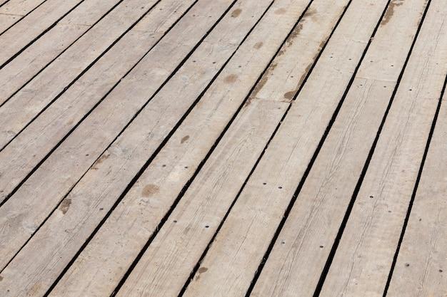 Assi del pavimento nel gazebo. piano in legno oscurato dall'ambiente. foto da vicino