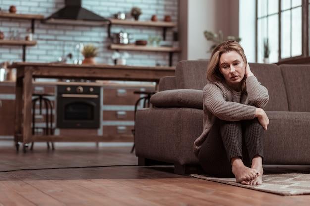 Sul pavimento. moglie matura depressa seduta sul pavimento mentre si sente stressata dopo una discussione in famiglia