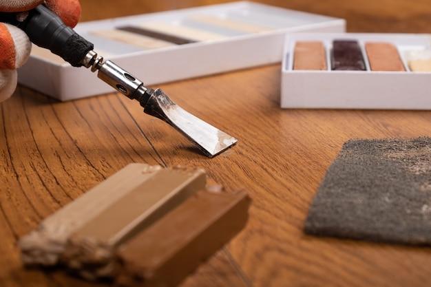 Restauro pavimenti con cera, riparazione difetti su laminato, primo piano parquet.