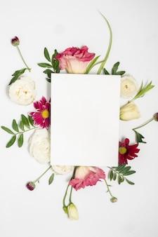 Addobbo floreale e carta in bianco su sfondo bianco.
