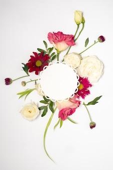 Disposizione floreale e carta rotonda in bianco su una superficie bianca.