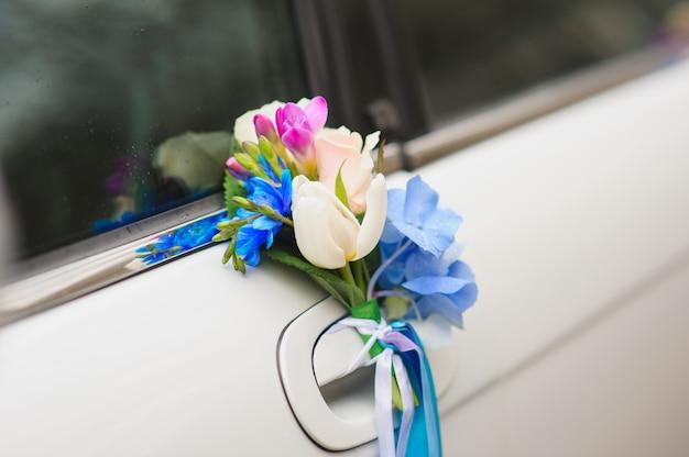 Composizione floreale sulla maniglia dell'auto