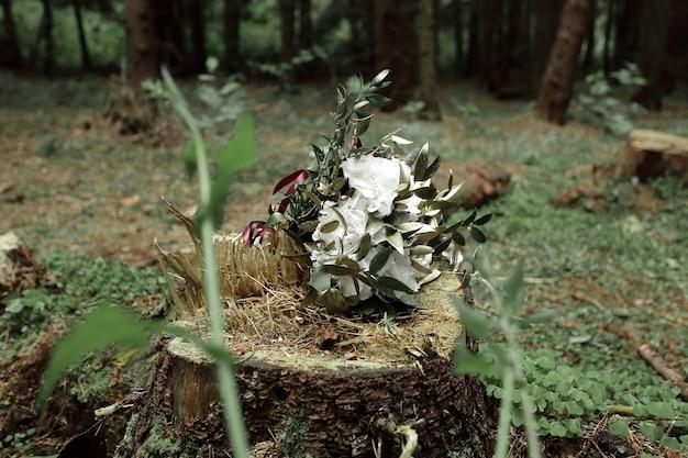 Addobbo floreale su un ceppo nel bosco.