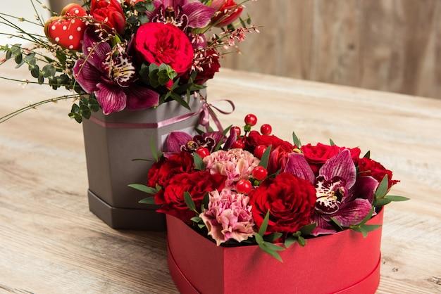 Composizioni floreali in scatole sul tavolo di legno