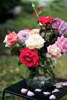 Bouquet floreale di diverse rose colorate in un vaso di vetro su un tavolo scuro con petali caduti.