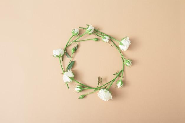 Cerchio floreale su sfondo marrone chiaro beige. cornice rotonda di rose bianche. composizione di arte floreale minimalista