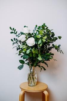 Composizione floreale all'interno. mazzo con rose bianche e foglie verdi. fiori in ciotola del fiore con acqua sulla tavola di legno.
