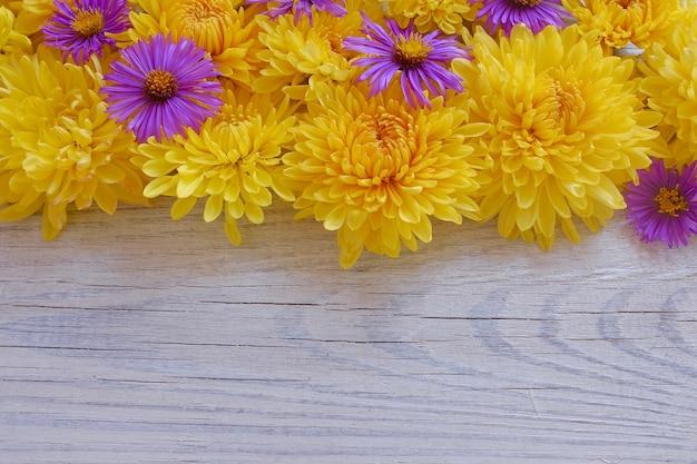 Cornice floreale di crisantemi su uno sfondo di legno bianco. copia spazio e vista dall'alto.