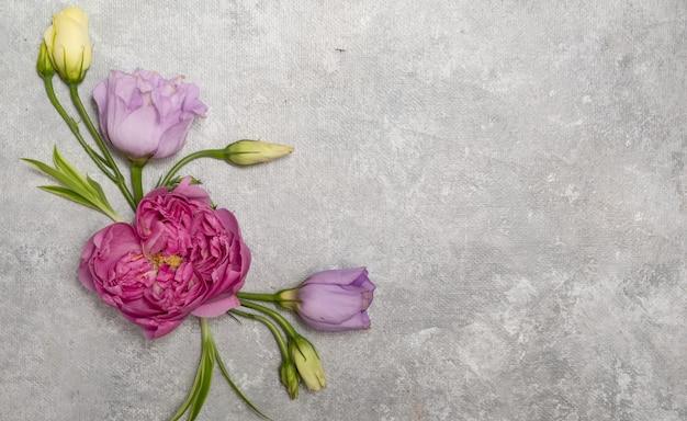 Cornice floreale su sfondo grigio. vista dall'alto e copia spazio. delicate rose lilla ed eustoma. composizione ad angolo. foto di alta qualità