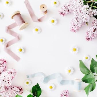 Cornice floreale di fiori lilla camomilla rami freschi e rocchetto con nastro blu e beige su sfondo bianco vista dall'alto piatta
