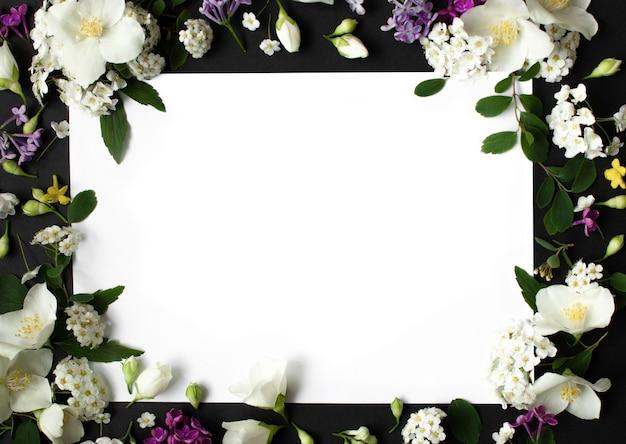 Cornice floreale fatta di diversi fiori primaverili su sfondo nero fiori spazio piatto per il testo