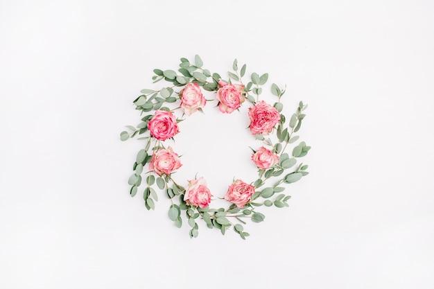 Corona di cornice floreale fatta di fiori di rosa rossa e rami di eucalipto isolati su priorità bassa bianca. disposizione piatta, vista dall'alto